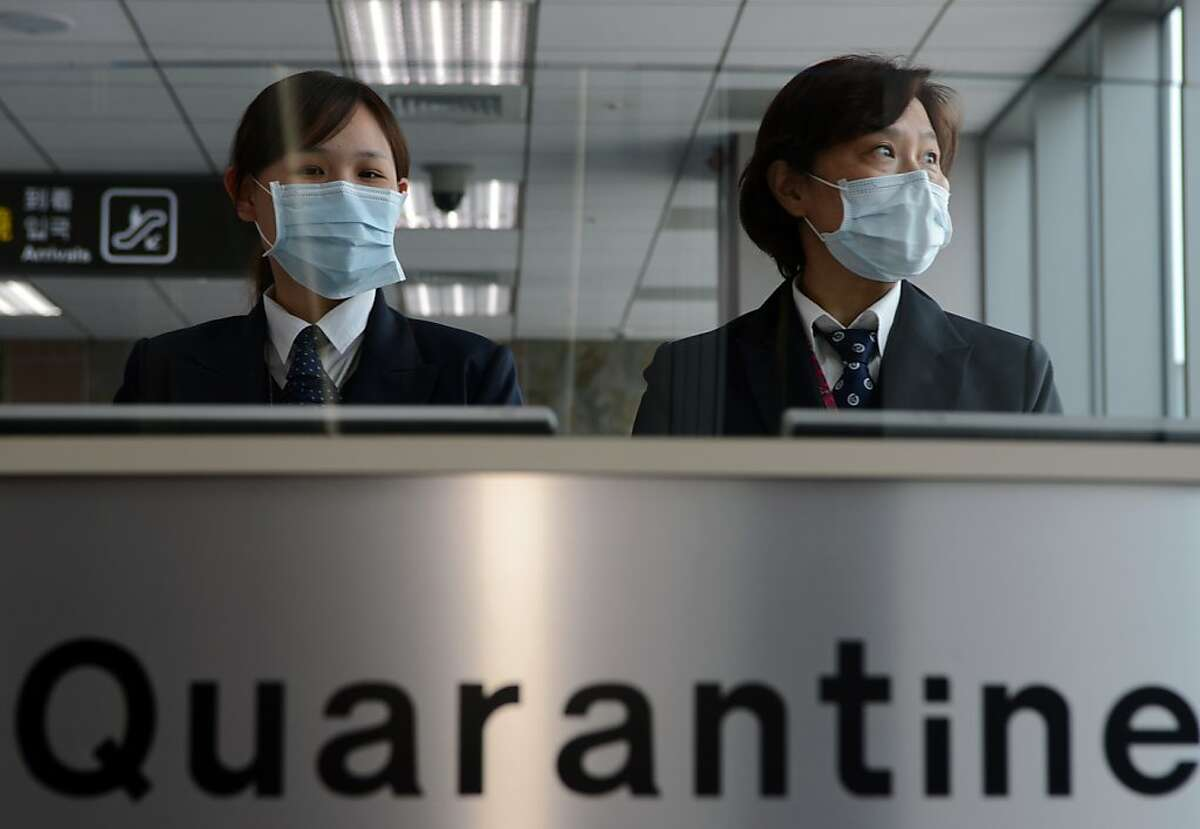 Taiwan's Center for Disease Control (CDC) staff stand at the entrance of Sungshan Airport in Taipei
