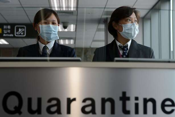 Taiwan's Center for Disease Control (CDC) staff stand at the entrance of Sungshan Airport in Taipei on April 4, 2013. Taiwan enhanced its level of alert against bird flu and set up a contingency centre after China's report of seven people infected with a new strain of avian influenza, including two deaths.