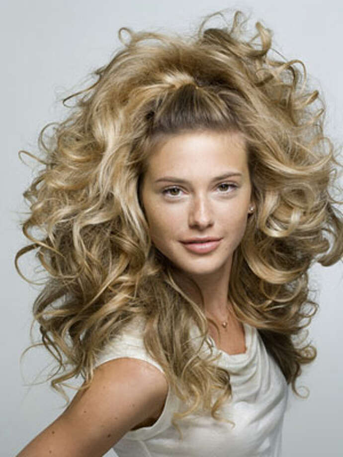 Bold BouffantHow to Get the Look:  Step 1: For big curls, blow-dry just-washed hair haphazardly until it\'s almost dry. Then wrap two-inch sections of hair around medium-size hot rollers — you\'ll need about 12 for this look. Let them sit for 20 minutes. Unwrap them carefully, and brush through to expand curls.  Step 2: Use a round brush to smooth back a three-inch-wide section of hair along your hairline in the front. Brush the piece back tightly, and secure on each side with a bobby pin that matches your hair color.  Step 3: Hold your style in place by spritzing a volumizing hairspray all over — apply it from about eight inches away as you scrunch the ends.