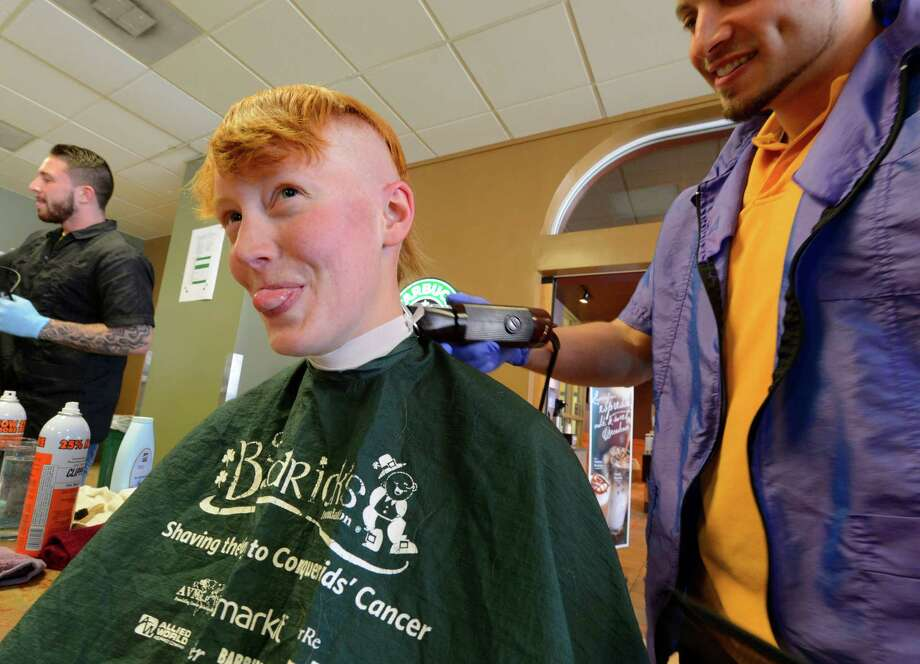 Dani Dayton sticks her tongue out at some of her friends as she sheds her hair to benefit St. Baldrick's Foundation on Thursday at The College of St. Rose.  The foundation is a childhood cancer charity. (Skip Dickstein / Times Union) Photo: SKIP DICKSTEIN