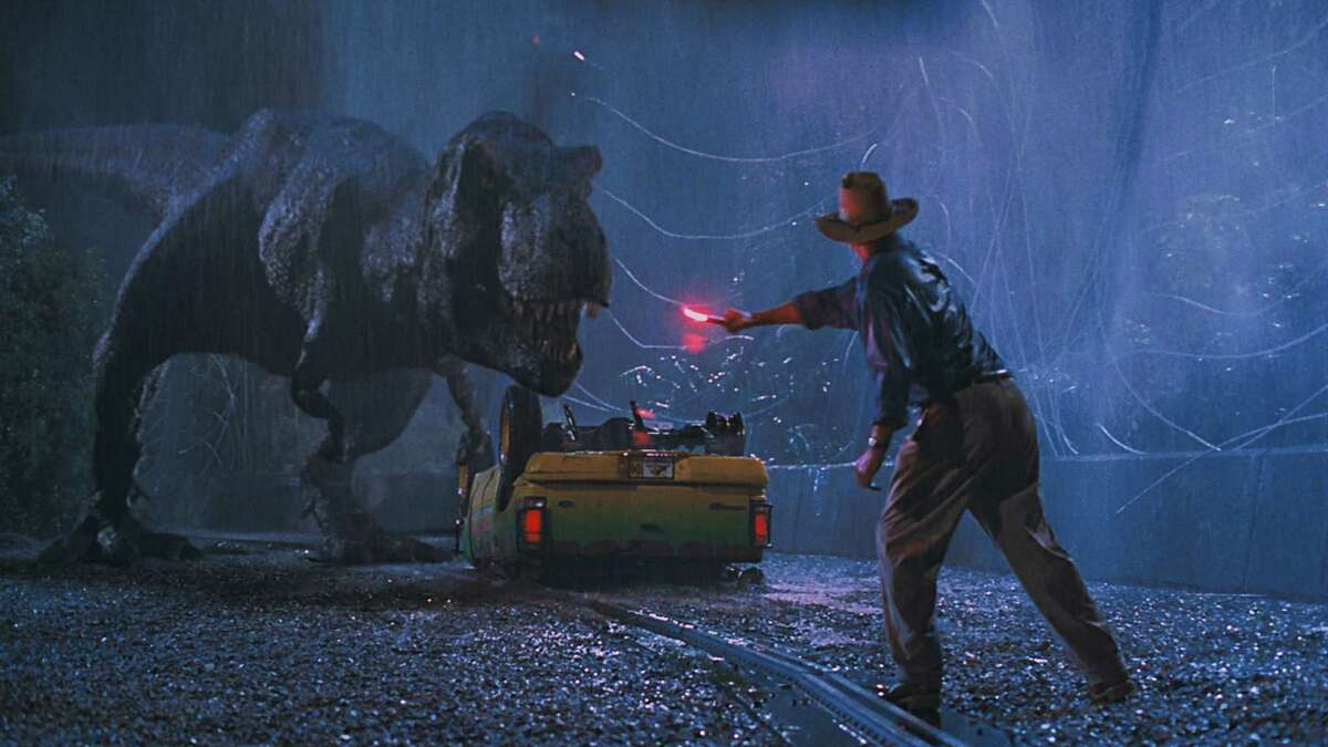 """Dr. Alan Grant (Sam Neill) tries to distract a hungry T. rex in Steven Spielberg's """"Jurassic Park 3-D."""""""