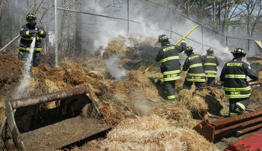 Firefighters knock down a fire that erupted in a barrier of hay bales at a Weston Road construction site Thursday afternoon. WESTPORT NEWS, CT 4/4/13 Photo: Westport Fire Department / Westport News contributed