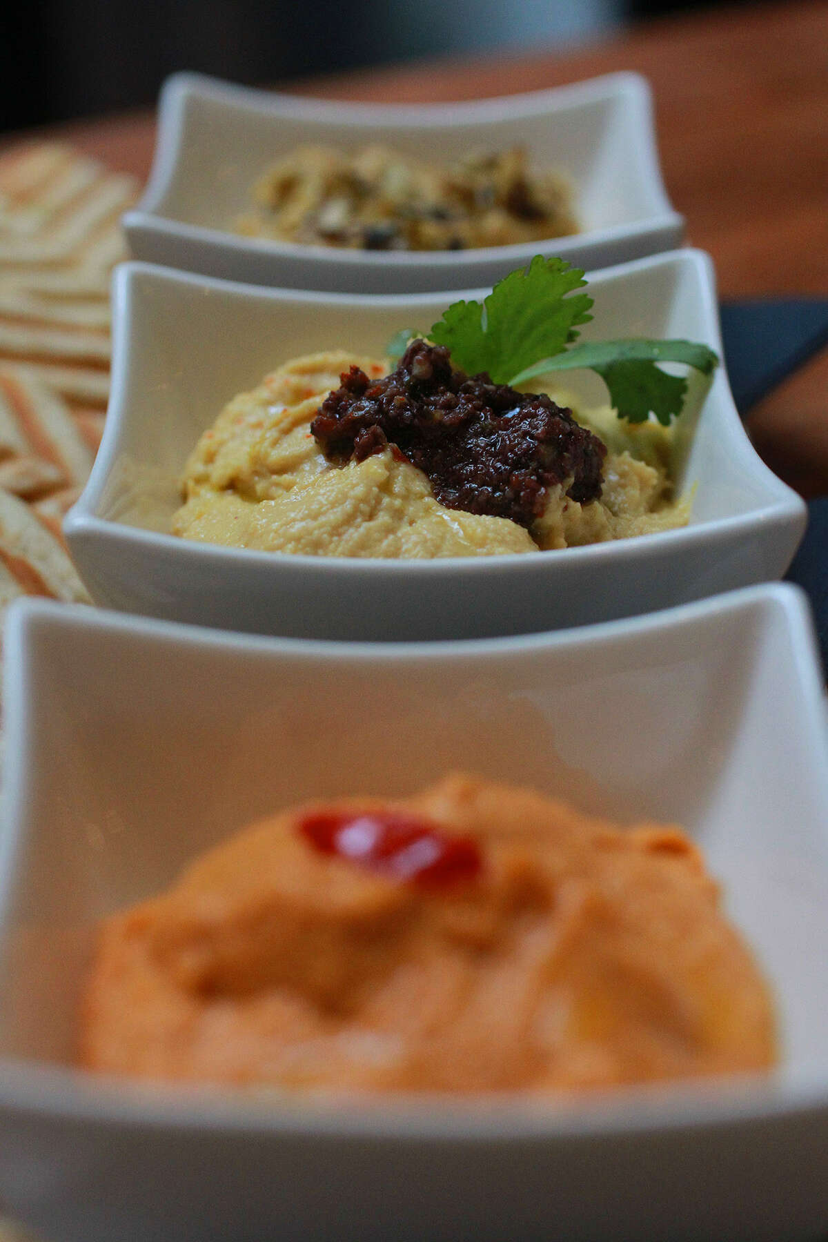 The Hummus Trio appetizer includes classic, roasted red pepper and artichoke varieties.