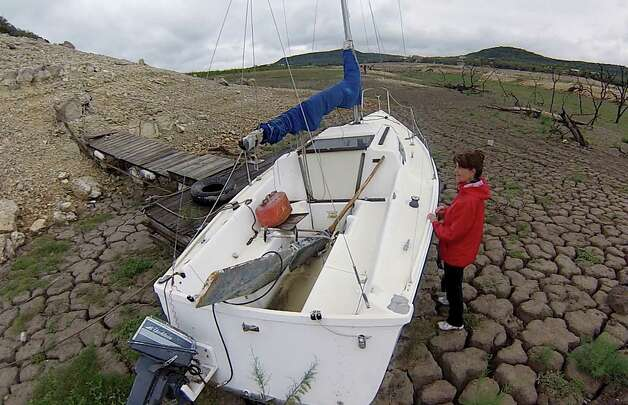Karen Ripley, a resident of the Medina Lake area, investigates a boat left on the bottom by the receding waters of Elm Cove, a portion of Medina Lake, on Wednesday, April 3, 2013. Photo: Billy Calzada, San Antonio Express-News / San Antonio Express-News