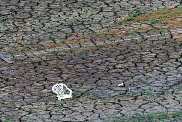 A chair and other debris sit on the dry bottom of Medina Lake at Elm Cove on Wednesday, April 3, 2013. Photo: Billy Calzada, San Antonio Express-News / San Antonio Express-News