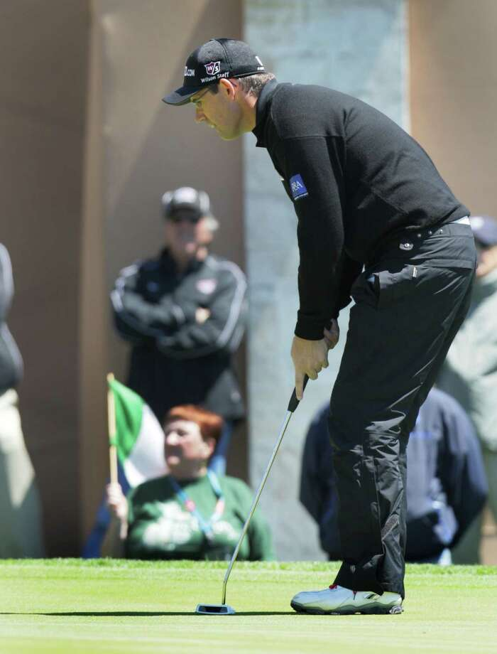 Padraig Harrigton lines up a putt on the 18th which he bogied, as a woman behind him holds an Irish flag, during the first round of the Valero Texas Open.  Thursday April 4, 2013. He is in the clubhouse with a 4 under par after the first round. Photo: Bob Owen, Express-News / ©2013 San Antonio Express-News
