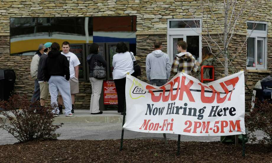 In this Friday, March 29, 2013, people line up outside a restaurant in front of a help wanted sign in Richmond, Va. The number of Americans seeking unemployment aid rose to a four-month high in the week ending March 30, 2013, although the increase partly reflects seasonal distortions around the spring holidays. The Labor Department says weekly applications increased 28,000 to a seasonally adjusted 385,000. That is the highest level since late November. The four-week average, a less volatile measure, rose to 354,250.  (AP Photo/Steve Helber) Photo: Steve Helber