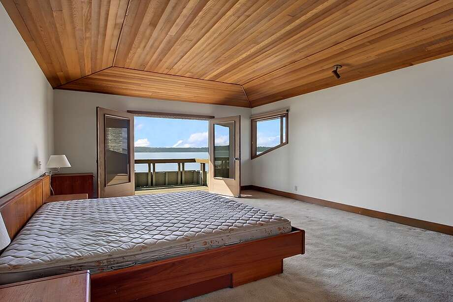 Master bedroom of 11065 Arroyo Beach Place S.W., in Arbor Heights. The 2,950-square-foot home, built in 1977, has four bedrooms, 2.5 bathrooms, wood walls, vaulted wood ceilings, two stone fireplaces, walls of windows overlooking Puget Sound, a rec room, decks, patios and a boat ramp on half an acre with 72 feet of waterfront. It's listed for $1.5 million. Want to see it? There's an open house scheduled from noon to 4 p.m. on Sunday. Photo: Courtesy David Katt/Prudential Northwest Realty Associates