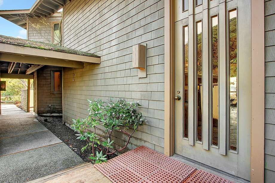 Entry of 11065 Arroyo Beach Place S.W., in Arbor Heights. The 2,950-square-foot home, built in 1977, has four bedrooms, 2.5 bathrooms, wood walls, vaulted wood ceilings, two stone fireplaces, walls of windows overlooking Puget Sound, a rec room, decks, patios and a boat ramp on half an acre with 72 feet of waterfront. It's listed for $1.5 million. Want to see it? There's an open house scheduled from noon to 4 p.m. on Sunday. Photo: Courtesy David Katt/Prudential Northwest Realty Associates