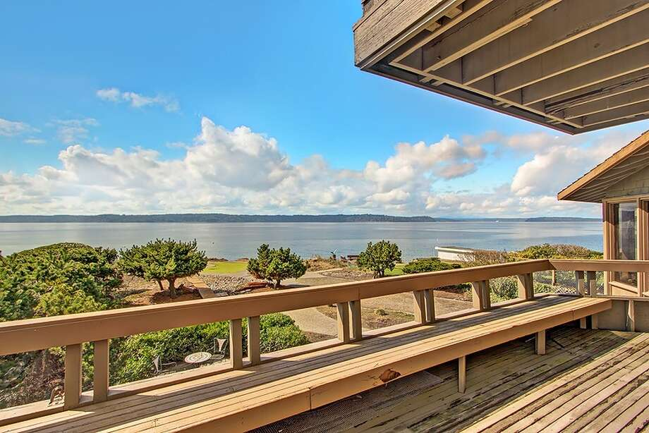 Deck of 11065 Arroyo Beach Place S.W., in Arbor Heights. The 2,950-square-foot home, built in 1977, has four bedrooms, 2.5 bathrooms, wood walls, vaulted wood ceilings, two stone fireplaces, walls of windows overlooking Puget Sound, a rec room, patios and a boat ramp on half an acre with 72 feet of waterfront. It's listed for $1.5 million. Want to see it? There's an open house scheduled from noon to 4 p.m. on Sunday. Photo: Courtesy David Katt/Prudential Northwest Realty Associates
