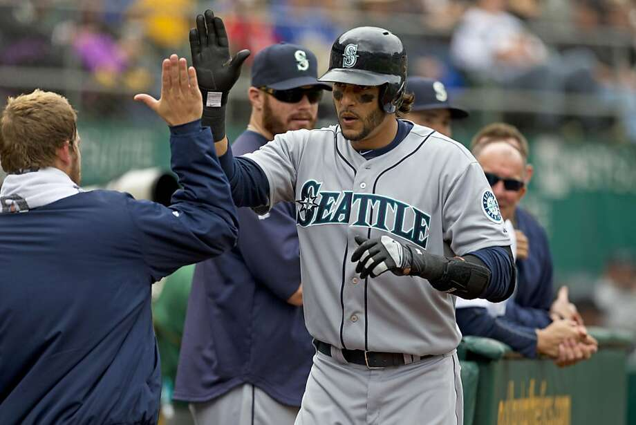 OAKLAND, CA - APRIL 04: Michael Morse #38 of the Seattle Mariners is congratulated by teammates in the dugout after hitting a home run against the Oakland Athletics during the sixth inning at O.co Coliseum on April 4, 2013 in Oakland, California. The Oakland Athletics defeated the Seattle Mariners 8-2. (Photo by Jason O. Watson/Getty Images) Photo: Jason O. Watson, Getty Images