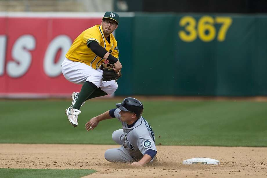 OAKLAND, CA - APRIL 04: Kyle Seager #15 of the Seattle Mariners disrupts a double play attempt by Eric Sogard #28 of the Oakland Athletics during the sixth inning at O.co Coliseum on April 4, 2013 in Oakland, California. The Oakland Athletics defeated the Seattle Mariners 8-2. (Photo by Jason O. Watson/Getty Images) Photo: Jason O. Watson, Getty Images
