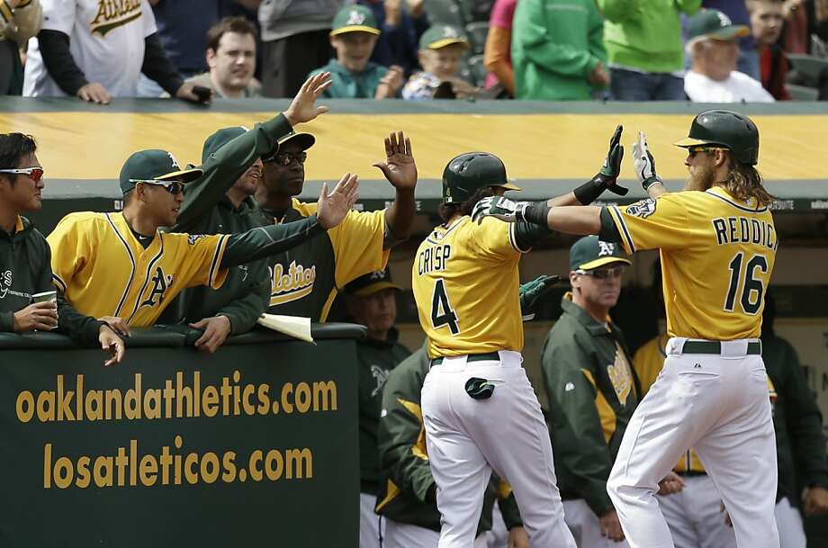 Oakland Athletics' Josh Reddick (16) and Coco Crisp (4) celebrate after Crisp scored against the Seattle Mariners in the eighth inning of a baseball game, Thursday, April 4, 2013, in Oakland, Calif. Crisp scored on a sacrifice fly hit by Reddick. (AP Photo/Ben Margot) Photo: Ben Margot, Associated Press