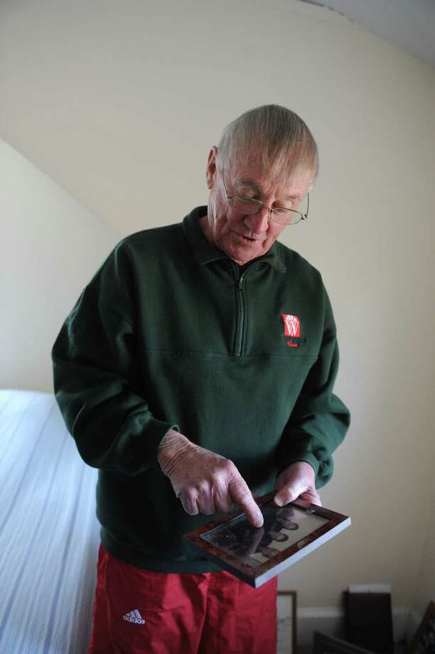 Tom Harrington looks at a photograph at his home, in Cos Cob, Conn., April 4, 2013. Greenwich native Harrington, a now-retired nationally known college basketball referee who officiated many Final Four and national championship games. Photo: Helen Neafsey / Greenwich Time
