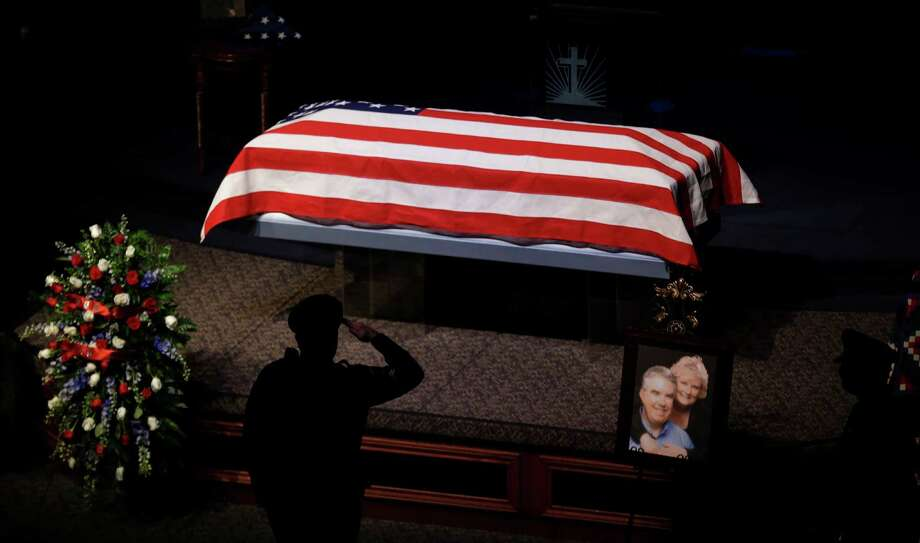 A police officer salutes as people file one-by-one past the remains of Kaufman County District Attorney Mike McLelland and his wife, Cynthia, during a memorial services in Mesquite, Texas, Thursday, April 4, 2013. Photo: LM Otero, Associated Press / AP