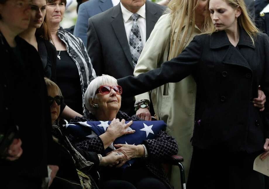 Shirley Woodward, mother of Cynthia McLelland, holds a flag and is comforted by family after memorial services for her daughter and son-in-law, Kaufman County District Attorney Mike McLelland, in Mesquite. Photo: LM Otero, Associated Press / AP