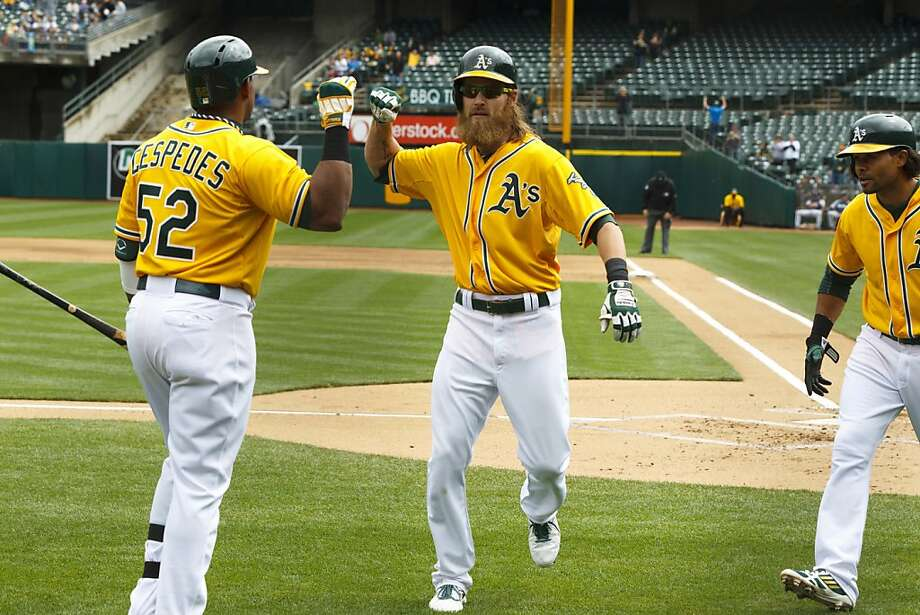 Josh Reddick is congratulated by Yoenis Céspedes after getting off the schneid with a two-run homer. Photo: Jason O. Watson, Getty Images