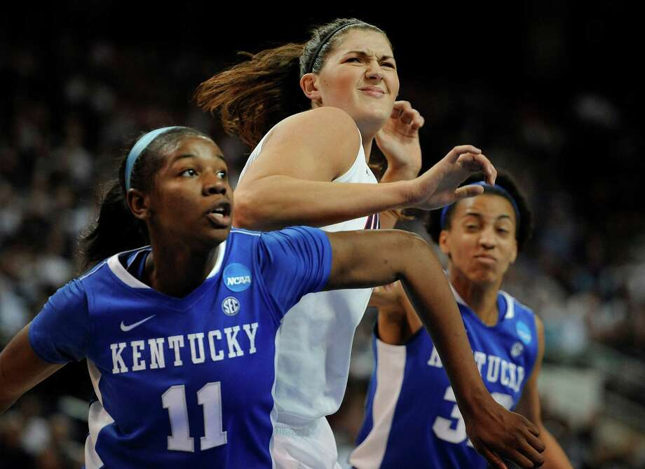 Connecticut's Stefanie Dolson, center positions for a rebound against Kentucky's DeNesha Stallworth, left, and Kentucky's Kastine Evans, right, during the second half of a regional final game in the NCAA college basketball tournament in Bridgeport, Conn., Monday, April 1, 2013. (AP Photo/Jessica Hill) Photo: Jessica Hill, Associated Press / FR125654 AP