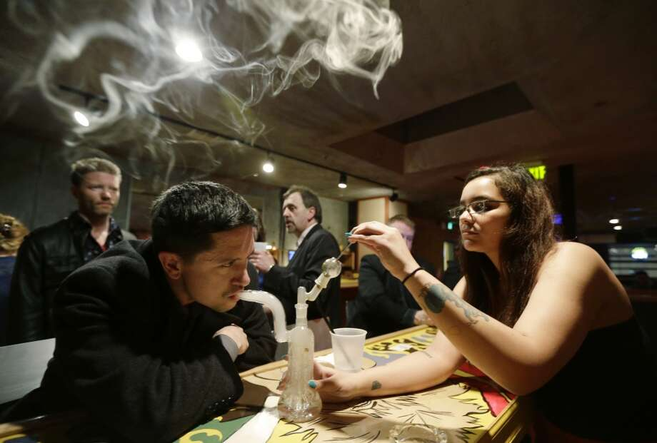 "John Connelly, left, inhales marijuana vapor just after midnight Saturday, March 2, 2013, with the help of bar worker Jenae DeCampo, right, in the upstairs lounge area of Stonegate, a pizza-and-rum bar in Tacoma, Wash. Owner Jeff Call charges patrons a small fee to become a member of the private second-floor club, which prohibits smoking marijuana, but does permit ""vaporizing,"" a method that involves heating the marijuana without burning it."