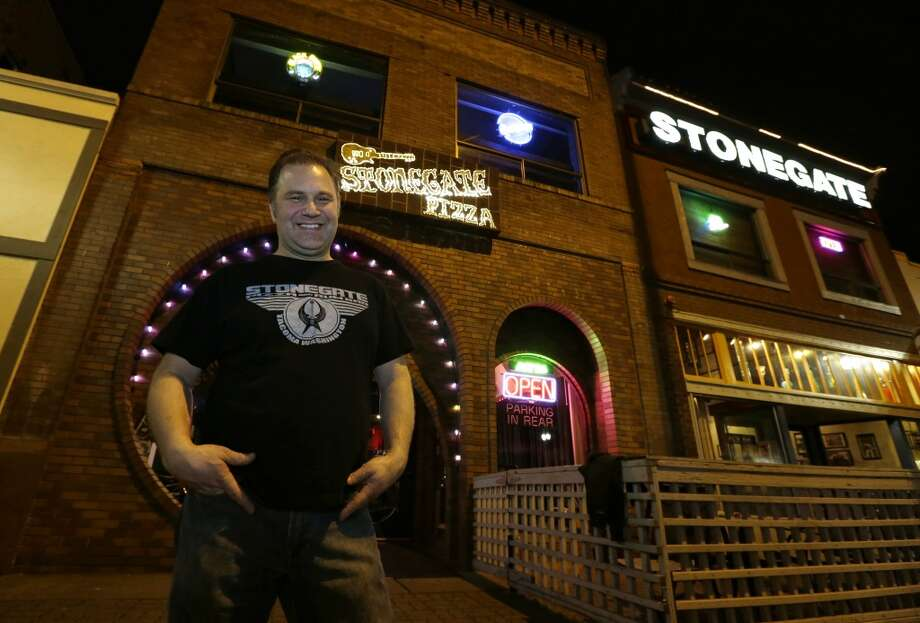 "Jeff Call, owner of the Stonegate pizza-and-rum bar, poses for a photo in front of his business, Saturday, March 2, 2013, in Tacoma, Wash. Call charges patrons a small fee to become a member of the private second-floor club in the lounge area upstairs, which allows ""vaporizing"" marijuana, a method that involves heating the marijuana without burning it."