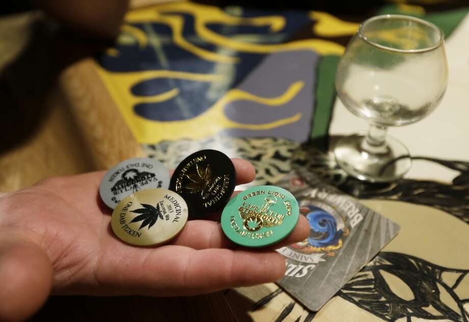 """Dab tokens,\"" which are exchanged for doses of marijuana vapor, are shown on the bar, Saturday, March 2, 2013, in the upstairs lounge area of Stonegate, a pizza-and-rum bar in Tacoma, Wash. Owner Jeff Call charges patrons a small fee to become a member of the private second-floor club, which prohibits smoking marijuana, but does permit ""vaporizing,"" a method that involves heating the marijuana without burning it."