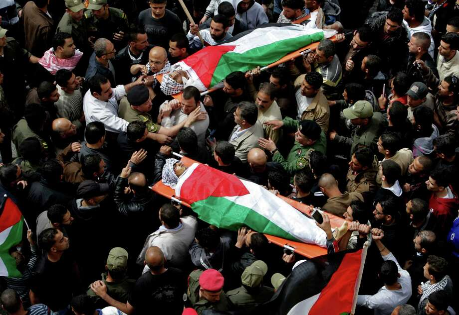 Palestinian mourners carry the bodies of Amer Nasser, top, and Naji Balbisi during their funeral in the West Bank town of Anabta, Thursday, April 4, 2013. Nasser and Balbisi were killed during clashes with Israeli security forces yesterday. (AP Photo / Nasser Ishtayeh) Photo: Nasser Ishtayeh