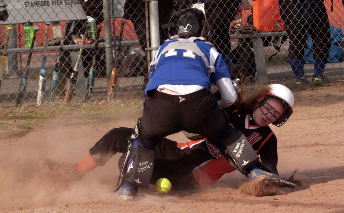 Stamford's Claire Kaptinski slides safely into home with resistance from Fairfield Ludlowe catcher Katie DeCarlo during their game at Stamford High School on Thursday, April 4, 2013. Fairfield Ludlowe won, 7-2.