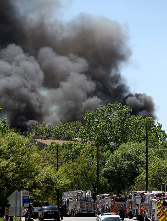 Smoke billows from the Castlewood Condominiums in the 4100 block of Medical Drive. A firefighter was injured when he fell 15 to 20 feet while seeking to rescue a resident from the third story of the condos. Photo: Photos By John Davenport / San Antonio Express-News
