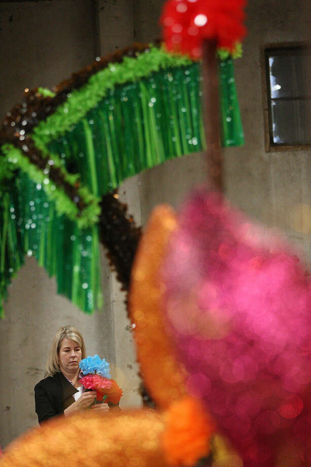 """Jennifer Harper arranges decorations at the Battle of Flowers Parade warehouse. This year's parade theme is """"Celebrations,"""" and the education floats represent festivals around the world."""