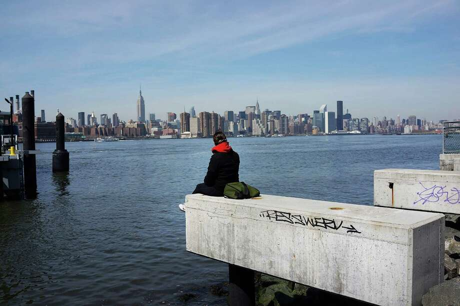 NEW YORK, NY - APRIL 04:  A person sits on the shore overlooking Manhattan while sitting along open space at the waterfront in the rapidly developing neighborhood of Williamsburg on April 4, 2013 in the Brooklyn borough of New York City. Two Trees management, which owns the closed Domino Sugar factory, has unveiled new plans for the site that will include more than half a million square feet of office space, 228,000 square feet of open space and 2,284 apartments and retail space. The plan is a continuation of the rapid development of the Williamsburg waterfront which offers Manhattan views and water taxis to other parts of New York City.  (Photo by Spencer Platt/Getty Images) *** BESTPIX *** Photo: Spencer Platt