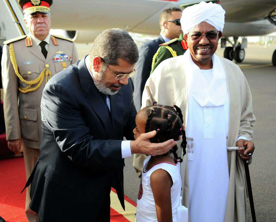 This image released by the Egyptian Presidency shows Mohammed Morsi greeting a girl after Sudan's President Omar al-Bashir, right, received him at the airport in Khartoum, Sudan, Thursday, April 4, 2013. Egyptian President Mohamed Morsi arrived in the Sudanese capital Khartoum on Thursday to meet the country's President Omar al-Bashir. (AP Photo/Egyptian Presidency) Photo: Anonymous