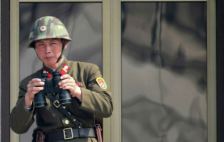 "A North Korean soldier watches the South Korean side at the border village of Panmunjom in the demilitarized zone (DMZ) in South Korea Thursday, April 4, 2013. South Korea's defense minister said Thursday North Korea has moved a missile with ""considerable range"" to its east coast, but said it is not capable of hitting the United States. (AP Photo/Yonhap, Lee Jong-hoon)  KOREA OUT Photo: Lee Jong-hoon"
