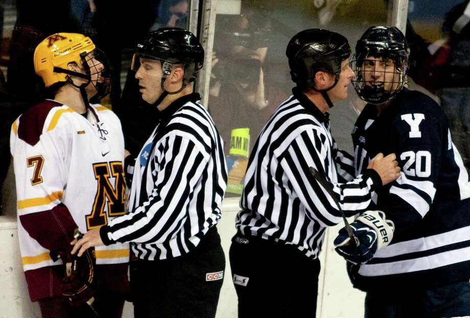 Officials separate Minnesota's Kyle Rau, left, and Yale's Jesse Root during the NCAA college hockey West Regional semifinals tournament game in Grand Rapids, Mich., Friday, March 29, 2013. Yale won 3-2 in overtime. (AP Photo/The Grand Rapids Press, Cory Morse) ALL LOCAL TV OUT; LOCAL TV INTERNET OUT. Photo: Cory Morse, Associated Press / The Grand Rapids Press
