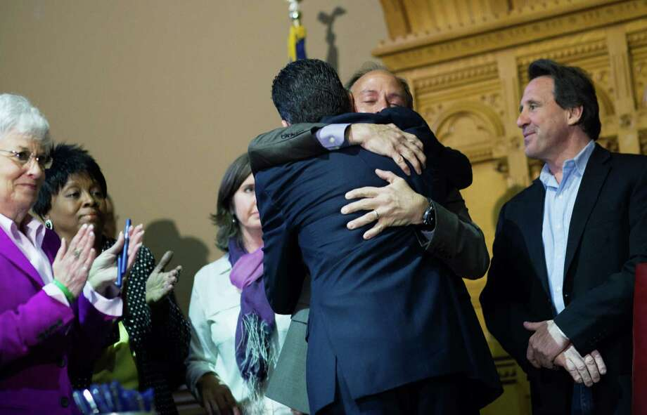 HARTFORD, CT - APRIL 4:  Connecticut Gov. Dannel Malloy (4th L) hugs Mark Barden (2nd R), the parent of a Sandy Hook shooting victim. after teh signing of a gun control law event at the Connecticut Capitol pril 4, 2013 in Hartford, Connecticut, After more than 13 hours of debate, the Connecticut General Assembly approved the gun-control bill early April 4, that proponents see as the toughest-in-the-nation response to the Demember 14, 2012 Newtown school shootings. (Photo by Christopher Capozziello/Getty Images) Photo: Christopher Capozziello