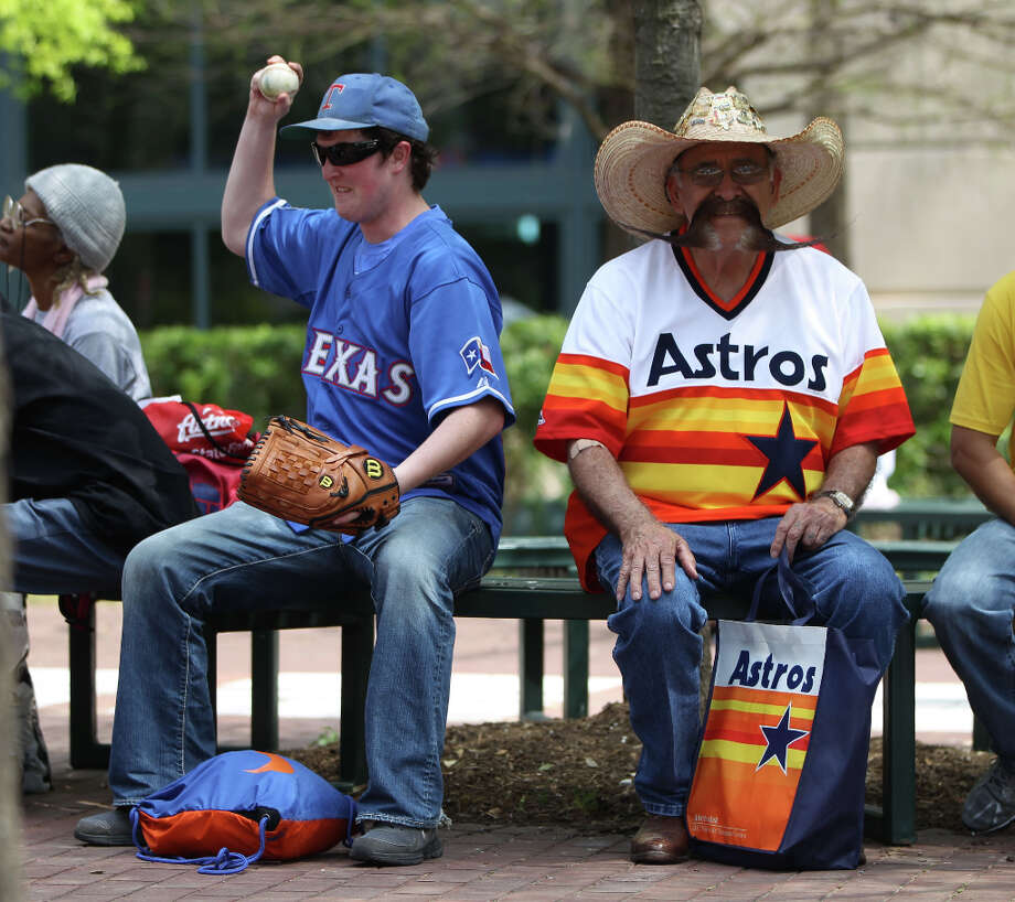 Tony Genna, left, a Rangers fan sits next Valentin Jalomo, an Astros fan, right, during the street festival. Photo: Karen Warren, Houston Chronicle / © 2013 Houston Chronicle