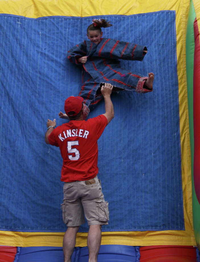 David Newsom, of New Caney, throws his daughter Brylee Newsom, 7, onto a velcro wall during the street festival. Photo: Karen Warren, Houston Chronicle / © 2013 Houston Chronicle