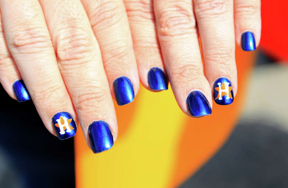 Jennifer Wiggins shows off her Astros nails during the street festival outside of Minute Maid Park. Photo: Karen Warren, Houston Chronicle / © 2013 Houston Chronicle
