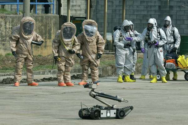 A bomb disposal robot has the attention of soldiers in the U.S. Army 23rd Chemical Battalion, wearing anti-chemical suits, during a demonstration Thursday.