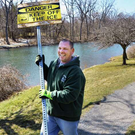 Sean Gaffney of Albany City Parks and Recreation removes thin-ice signs from around Buckingham Pond Thursday April 4, 2013.  (John Carl D'Annibale / Times Union) Photo: John Carl D'Annibale