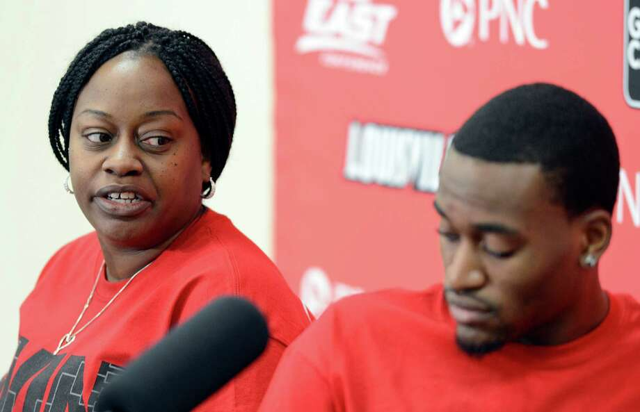 Louisville basketball player  Kevin Ware, right, looks down as his mother, Lisa Junior, answers questions during an interview Wednesday April 3, 2013, at the KFC Yum! Center practice facility in Louisville, Ky. Ware was released from an Indianapolis hospital Tuesday, two days after millions watched him break his right leg on a horrifying play trying to block a shot during an NCAA college basketball regional championship game against Duke.  (AP Photo/Timothy D. Easley) Photo: Timothy D. Easley / FR43398 AP