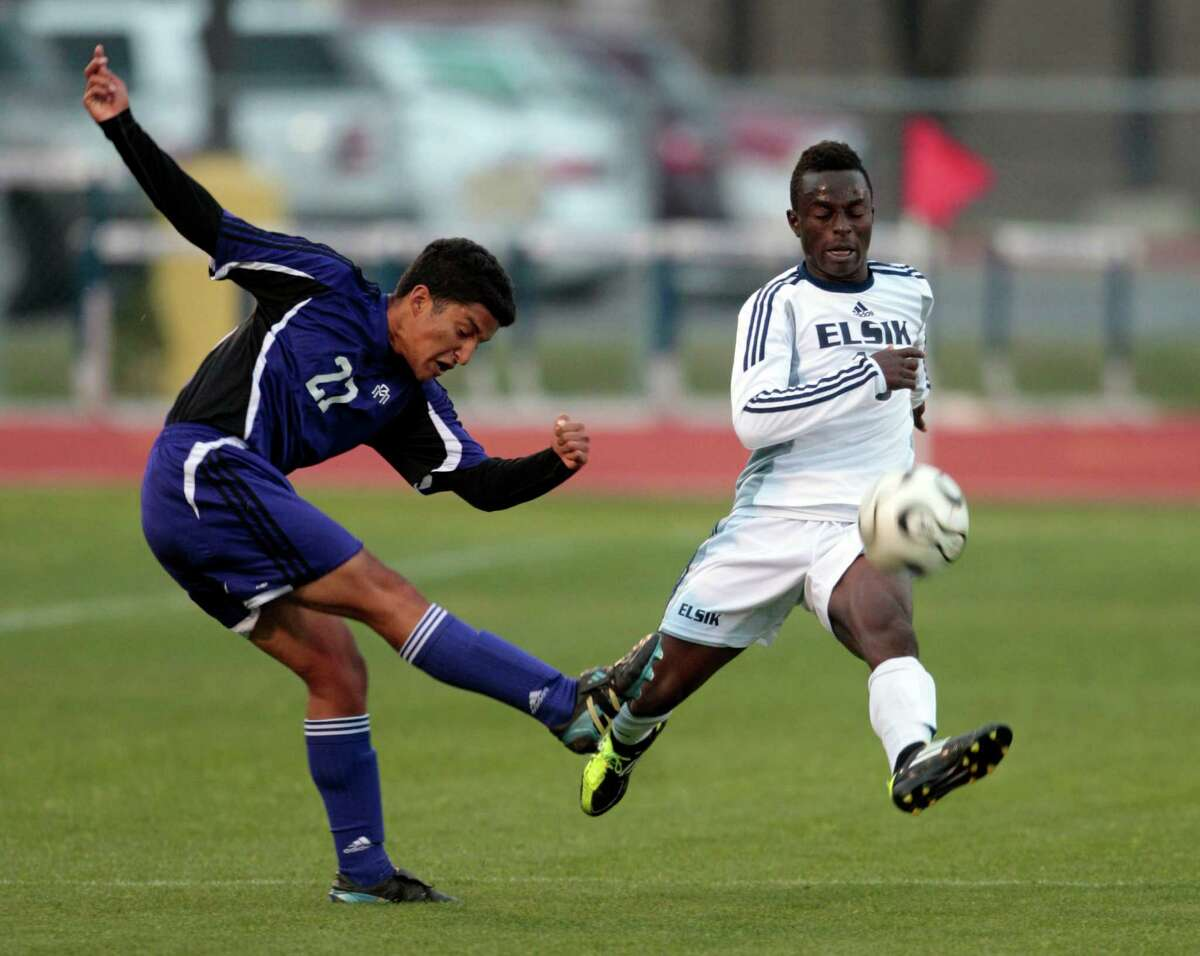 (l-r) Morton Ranch forward Carlos Aguilar kicks the ball as Elsik midfielder Williams Aniekan attempts to defend Thursday April 4, 2013 at Stratford High school during Elsik and Morton Ranch Class 5A area playoff round.