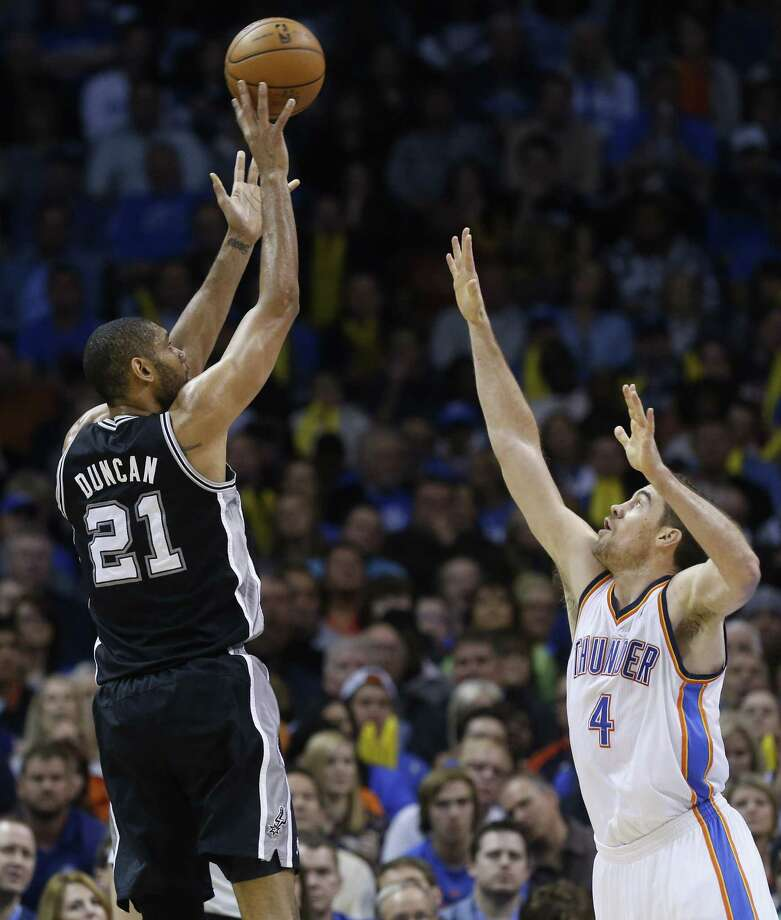 Tim Duncan shoots over the outstretched arm of Thunder forward Nick Collison in Oklahoma City. Duncan had another strong game, but the Spurs were unable to dig out of a 20-point hole. Photo: Sue Ogrocki / Associated Press