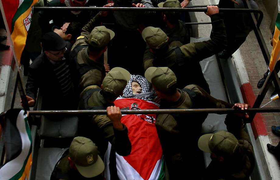 Palestinian police escort the body of Maysara Abu Hamdiyeh during his funeral in the West Bank city of Hebron, Thursday, April 4, 2013. Demonstrations first erupted across the West Bank on Tuesday over the death of a Palestinian prisoner who died from cancer. The  64-year-old prisoner, Hamdiyeh, was serving a life sentence for a 2002 foiled bombing of a busy Jerusalem cafe. After Abu Hamdiyeh died, the Palestinians blamed Israel for the death, saying he was not given proper medical care. Israel says the prisoner was treated by specialist doctors in hospital. (AP Photo/Nasser Shiyoukhi) Photo: Nasser Shiyoukhi, Associated Press