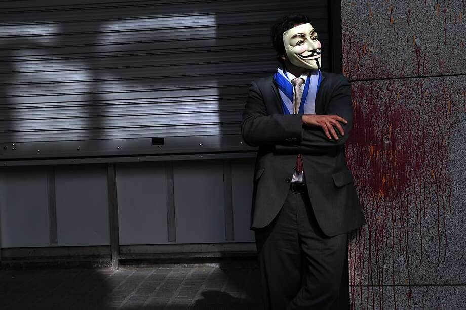 TOPSHOTS  A protester wearing a Guy Fawkes mask stands outside the Finance Ministry in Athens on April 4, 2013, as 'Independent Greeks' party members and supporters take part in a protest as they waited for the arrival of the EU-IMF-ECB troika,  whose meeting was finally rescheduled.  EU and IMF auditors are to meet Greek Finance Minister Yannis Stournaras later today, as they resume an audit suspended days before the eruption of the banking crisis in Cyprus.  AFP PHOTO/ LOUISA GOULIAMAKILOUISA GOULIAMAKI/AFP/Getty Images Photo: Louisa Gouliamaki, AFP/Getty Images