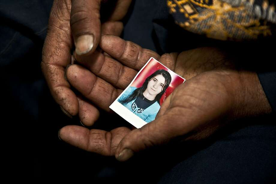 A father's pain:In the Minya town of Matai, Egypt, Christian farmer Ishaq Aziz cradles a picture of his daughter, 17-year-old Nirmeen, who went missing on Valentine's Day and has not been heard of or seen since. An Interior Ministry official said there have been at least 150 cases of Christian kidnappings in Minya since Mubarak was ousted two years ago. Photo: Thomas Hartwell, Associated Press
