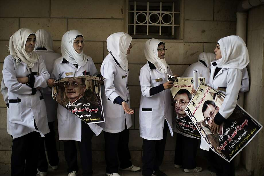 TOPSHOTS Palestinian nurses hold posters of Maisara Abu Hamdiyeh, a Palestinian prisoner who died of cancer while in Israeli detention, outside Al-Ahli hospital in the West Bank city of Hebron ahead of his funeral on April 4, 2013. The Palestinian leadership has accused Israel of medical negligence, despite moves by the prison service to secure his early release on compassionate grounds, with news of his death sparking angry clashes with the army, notably in Hebron. AFP PHOTO/MARCO LONGARIMARCO LONGARI/AFP/Getty Images Photo: Marco Longari, AFP/Getty Images