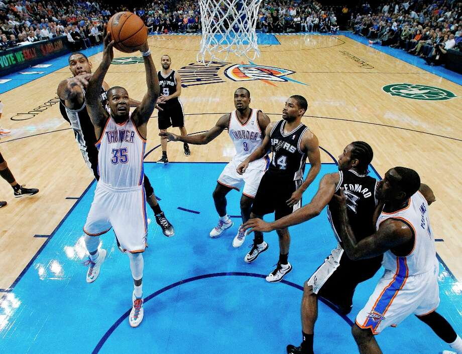 Oklahoma City Thunder forward Kevin Durant (35) shoots between Spurs forward Tim Duncan (left) and guard Gary Neal (14) in the second quarter in Oklahoma City, Thursday, April 4, 2013. Photo: Sue Ogrocki, Associated Press / AP