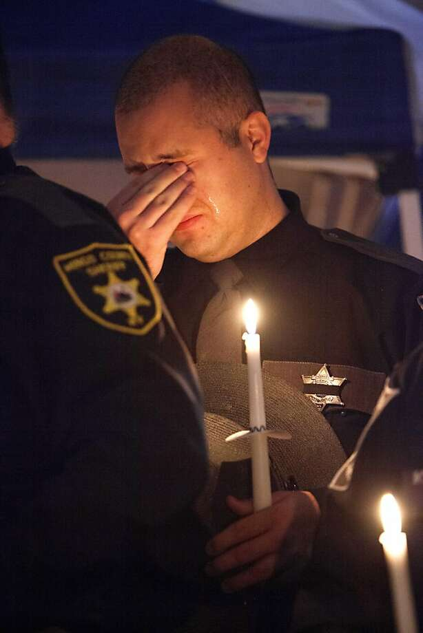 A Mingo County Sheriff's deputy weeps as friends, family and community leaders gathered on Thursday, April 4, 2013, in Williamson, W.Va. for a candlelight vigil honoring Mingo County Sheriff Eugene Crum who was gunned down after just three months in office. During the service, his wife Rosie Crum was sworn in as the new sheriff. She is Mingo County's first female sheriff. (AP Photo/Randy Snyder) Photo: Randy Snyder, Associated Press