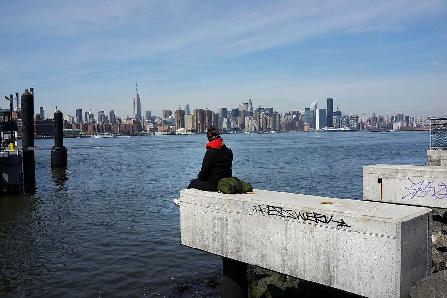 NEW YORK, NY - APRIL 04:  A person sits on the shore overlooking Manhattan while sitting along open space at the waterfront in the rapidly developing neighborhood of Williamsburg on April 4, 2013 in the Brooklyn borough of New York City. Two Trees management, which owns the closed Domino Sugar factory, has unveiled new plans for the site that will include more than half a million square feet of office space, 228,000 square feet of open space and 2,284 apartments and retail space. The plan is a continuation of the rapid development of the Williamsburg waterfront which offers Manhattan views and water taxis to other parts of New York City.  (Photo by Spencer Platt/Getty Images) *** BESTPIX *** Photo: Spencer Platt, Getty Images