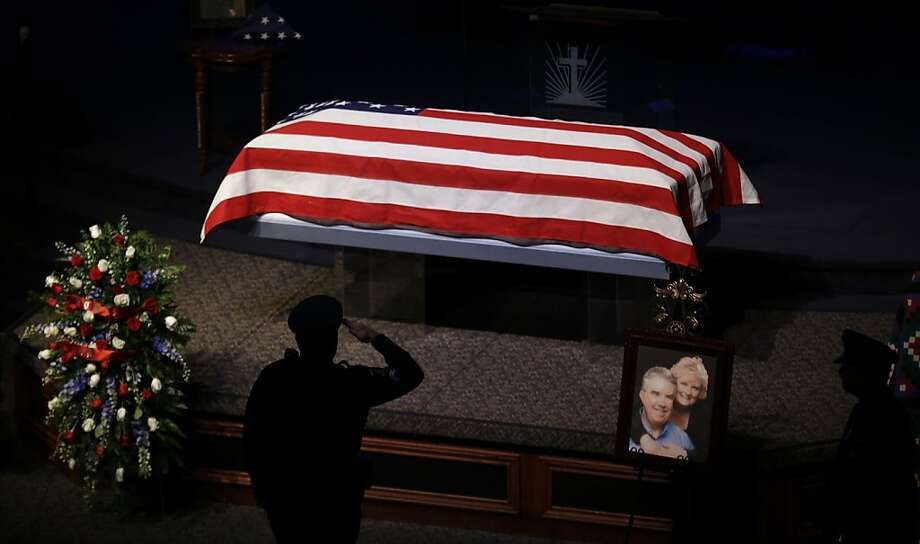 A police officer salutes as people file one-by-one past the remains of Kaufman County District Attorney Mike McLelland and his wife, Cynthia, during a memorial services in Mesquite, Texas, Thursday, April 4, 2013.  McLelland and his wife were found shot to death Saturday in their house near Forney, about 20 miles east of Dallas. No arrests have been made. (AP Photo/LM Otero) Photo: LM Otero, Associated Press